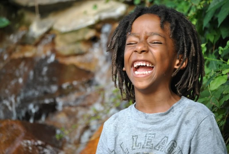 Boy standing outdoors laughing at snail jokes.