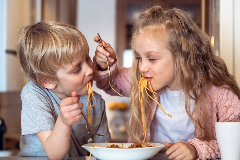 Little boy and girl amused while eating spaghetti.
