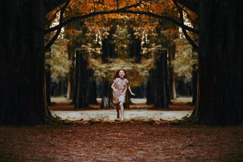 Young girl running through a path of trees.