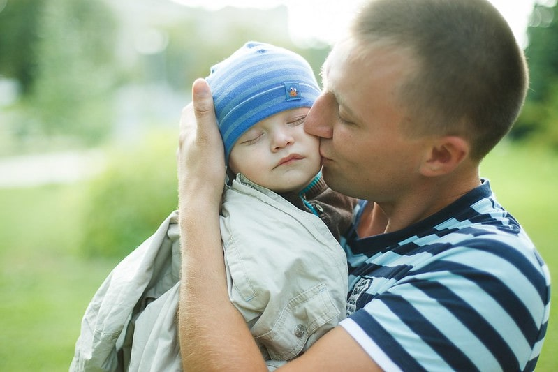 Dad holding baby boy in his arms kissing him.