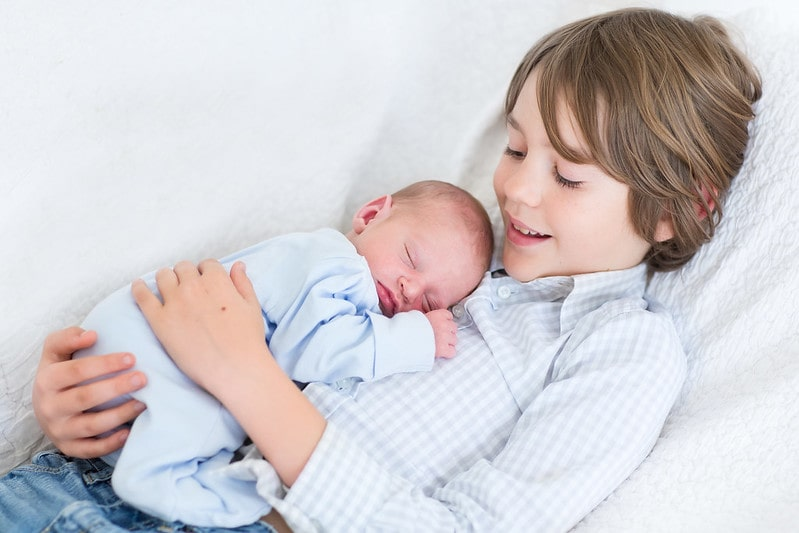 Boy holding sleeping newborn baby brother.
