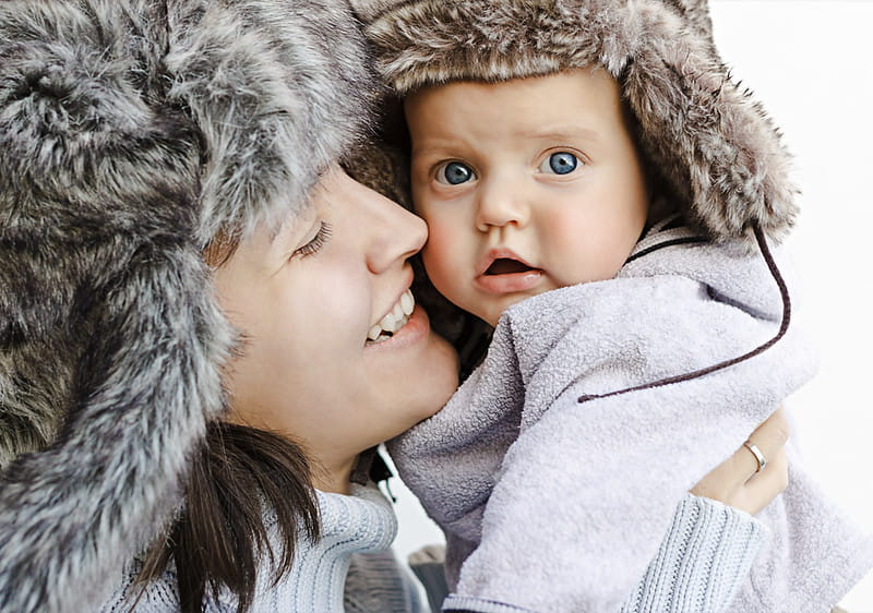 Mum and baby both wearing faux fur winter hats.