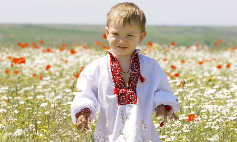 Baby boy in a field of flowers wearing traditional Russian clothes.