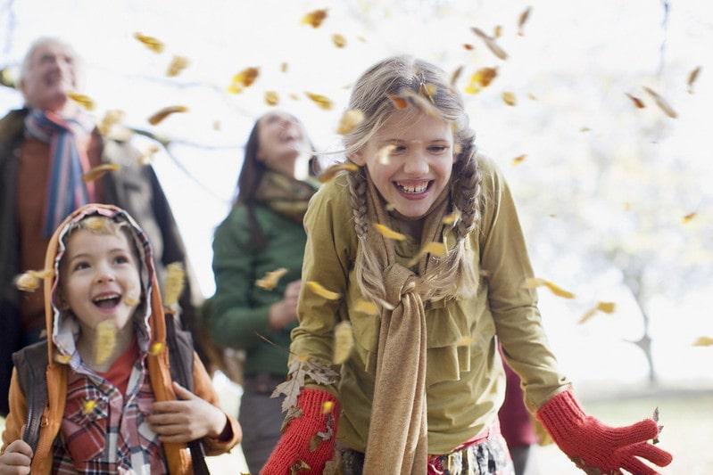 Kids smiling enjoying the orange leaves of autumn.