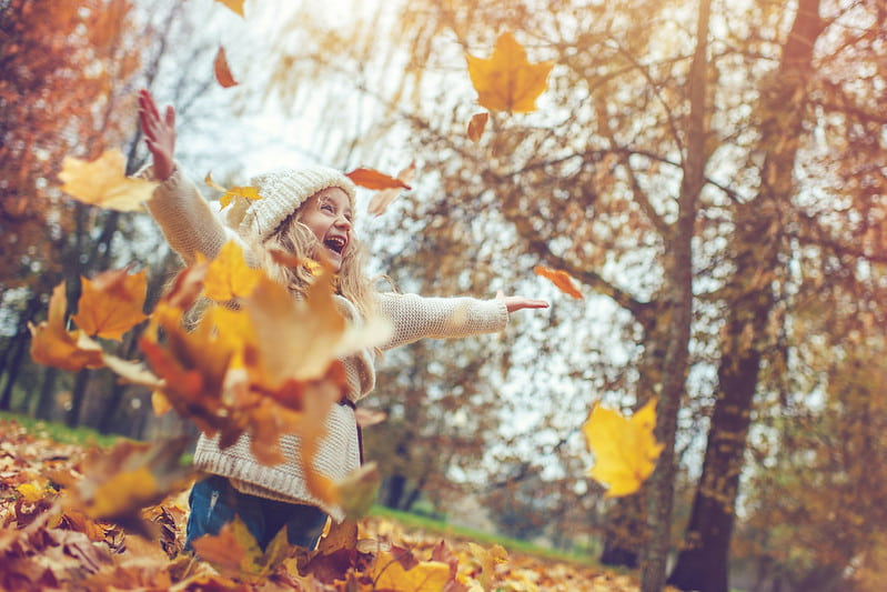 Happy girl smiling as she throws the autumn leaves up in the air.