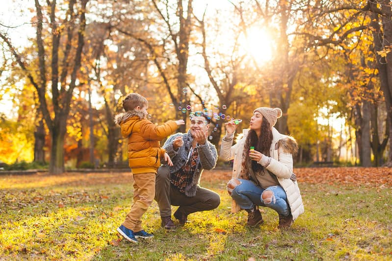 Family out in the park blowing bubbles and enjoying the autumn nature.