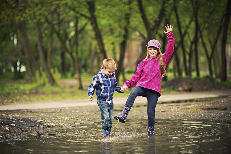 Girl and boy having fun splashing in a puddle.