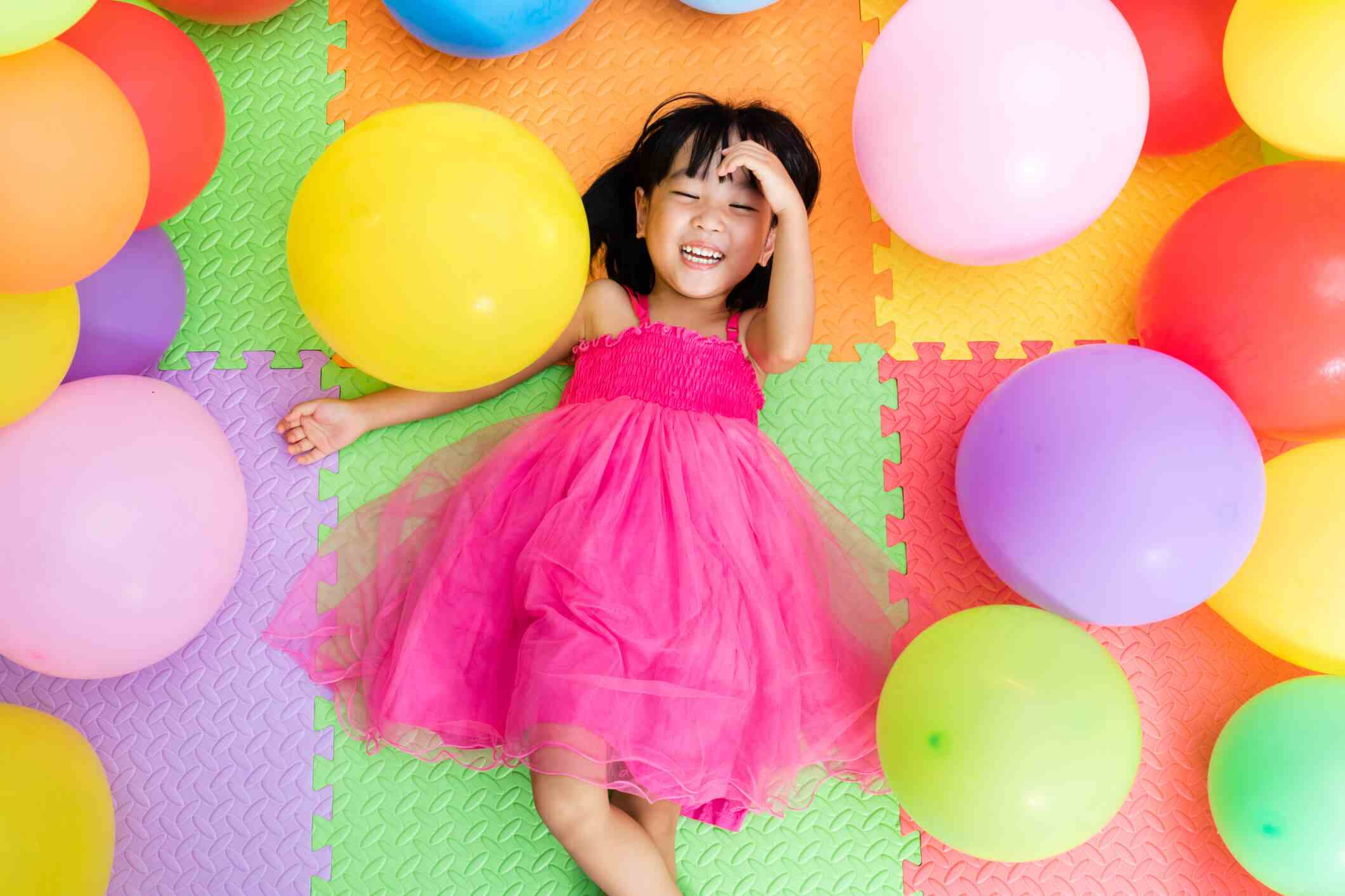 Girl surrounded by balloons.