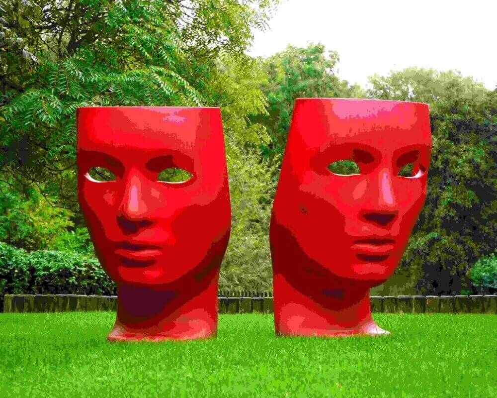 large sculpture of two red faces in a park