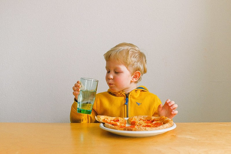 Young boy sat at the table eating pizza and drinking water.