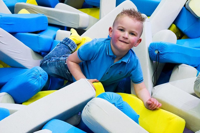 Boy in the pit of foam pads at the trampoline park.