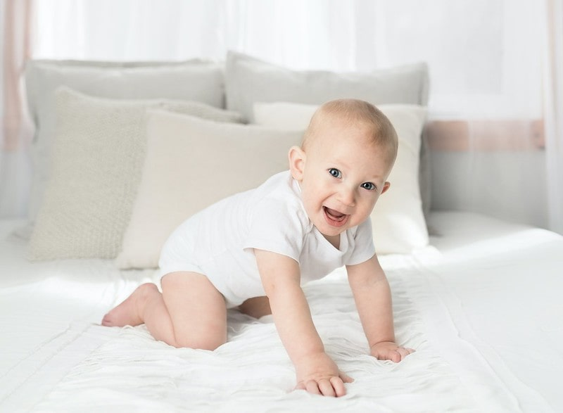 Baby wearing white crawling on the bed.