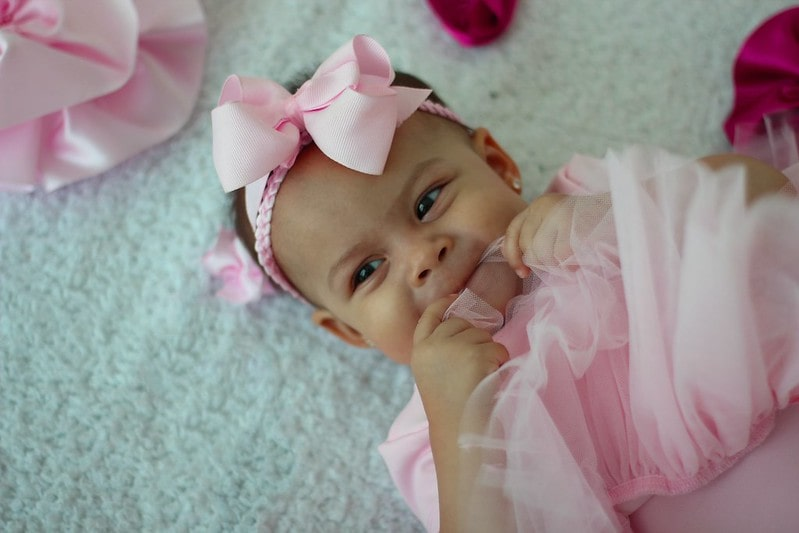 Baby girl wearing a pink bow bow headband, smiling.