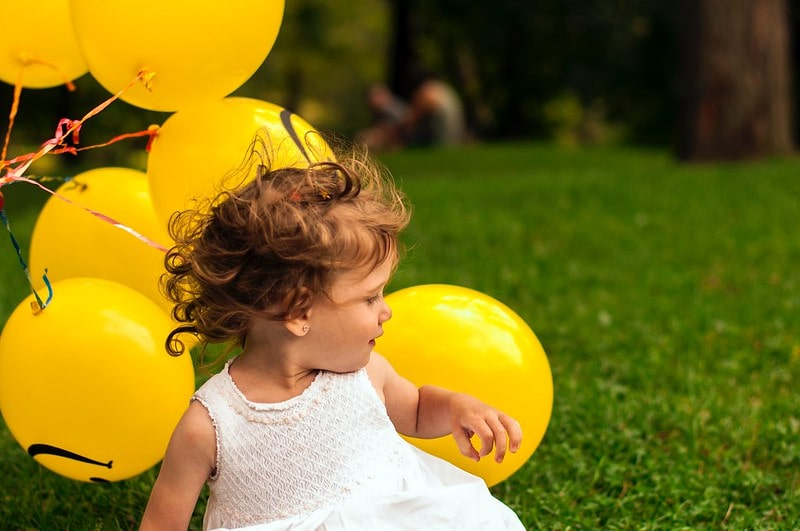 Little girl holding a bunch of yellow balloons.