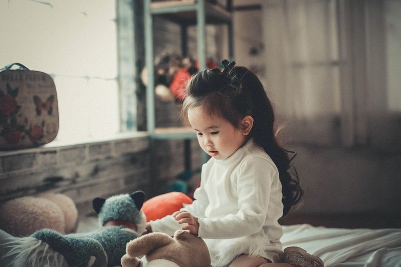 Little girl with long hair playing with teddy bears.