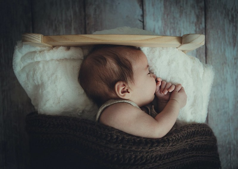 Baby sleeping in a cot with a brown blanket.