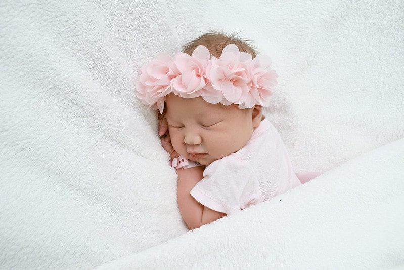 Baby girl wearing a pink flower crown sleeping on the bed.