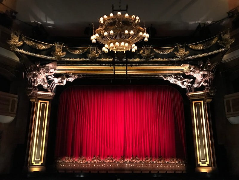 Red curtains over a theatre stage.