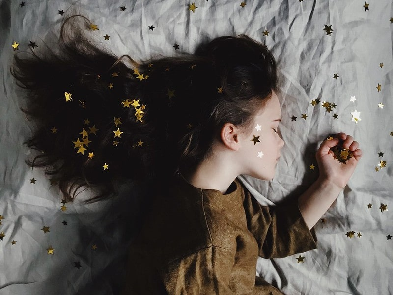 Young girl sleeping on the bed with gold stars on her face, hair and bed.