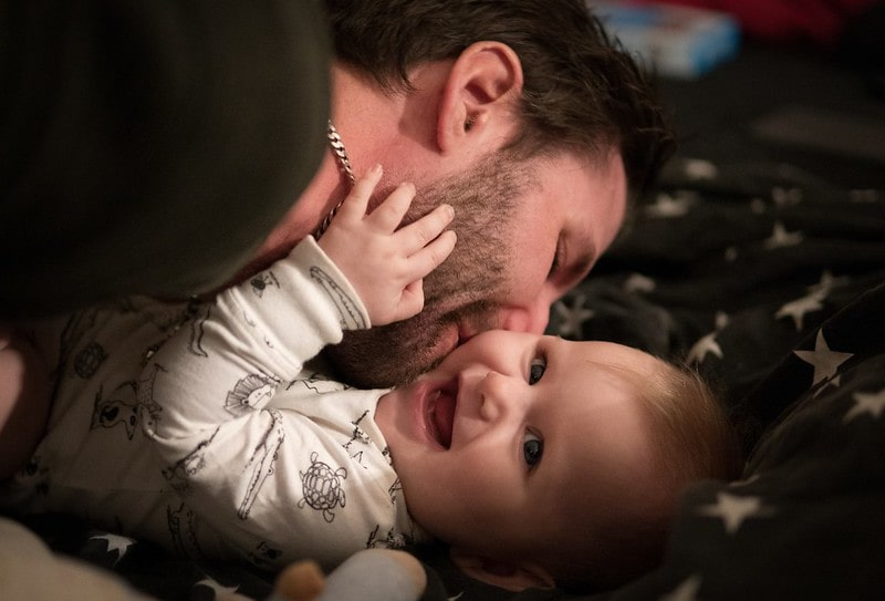 Dad kissing his smiling baby on their cheek, lying on a starry blanket.