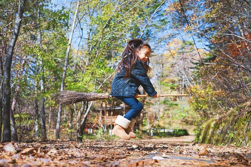 Little girl jumping on a broomstick in the woods.