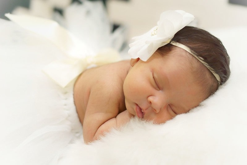 Newborn baby girl wearing a white flower headband sleeping.