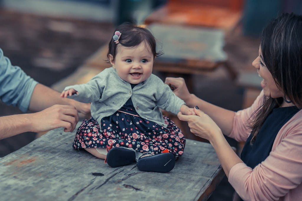 Baby girl in a floral dress and grey cardigan sat on a table smiling with her parents.