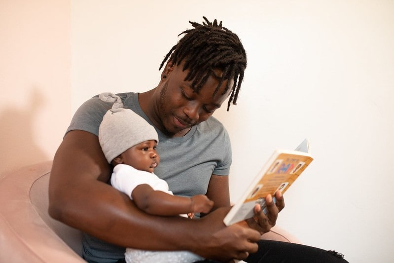 Dad reading a book to his baby son in his arms.