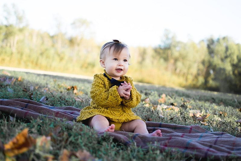 Baby girl wearing a yellow crochet dress sat on a rug on the lawn.