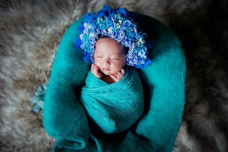Baby wearing a blue flower crown sleeping in a turquoise blanket.