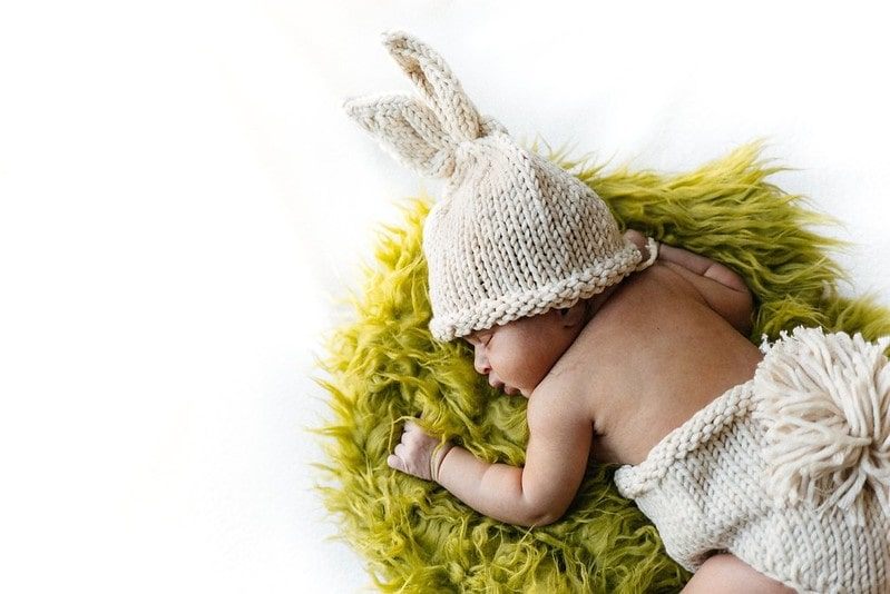 Baby wearing a knitted hat with bunny ears sleepy on a rug.