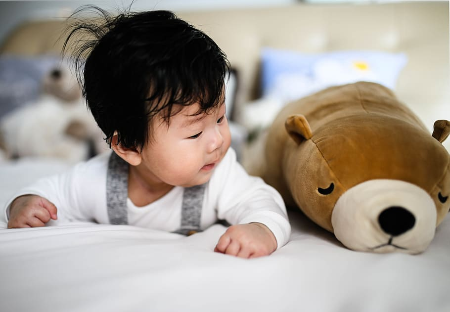 Baby boy lying on his tummy looking at a stuffed toy bear.