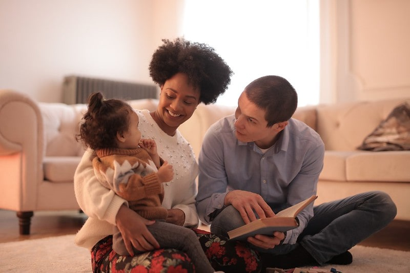 Parents reading to their baby girl.