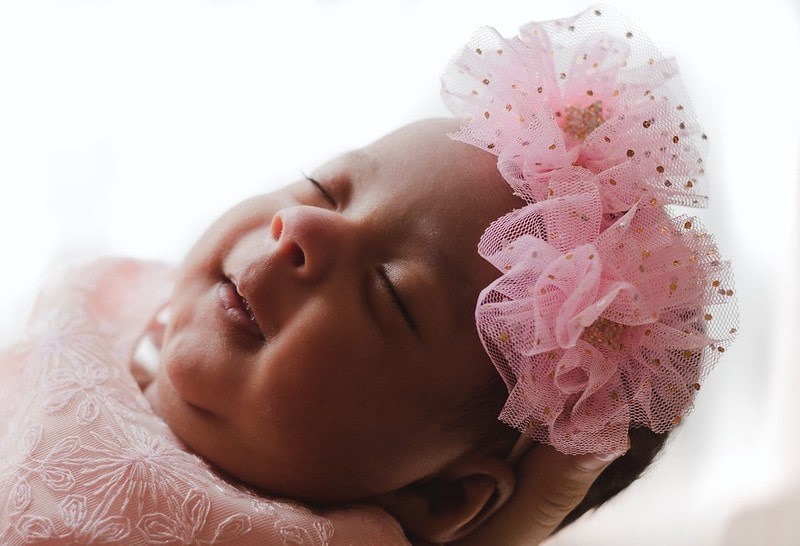 Sleeping baby girl wearing a pink net flower headband.