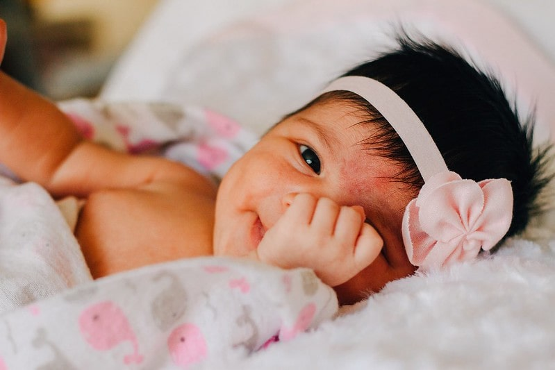 Baby girl wearing a flower hairband lying on the bed smiling, covering one eye with her hands.