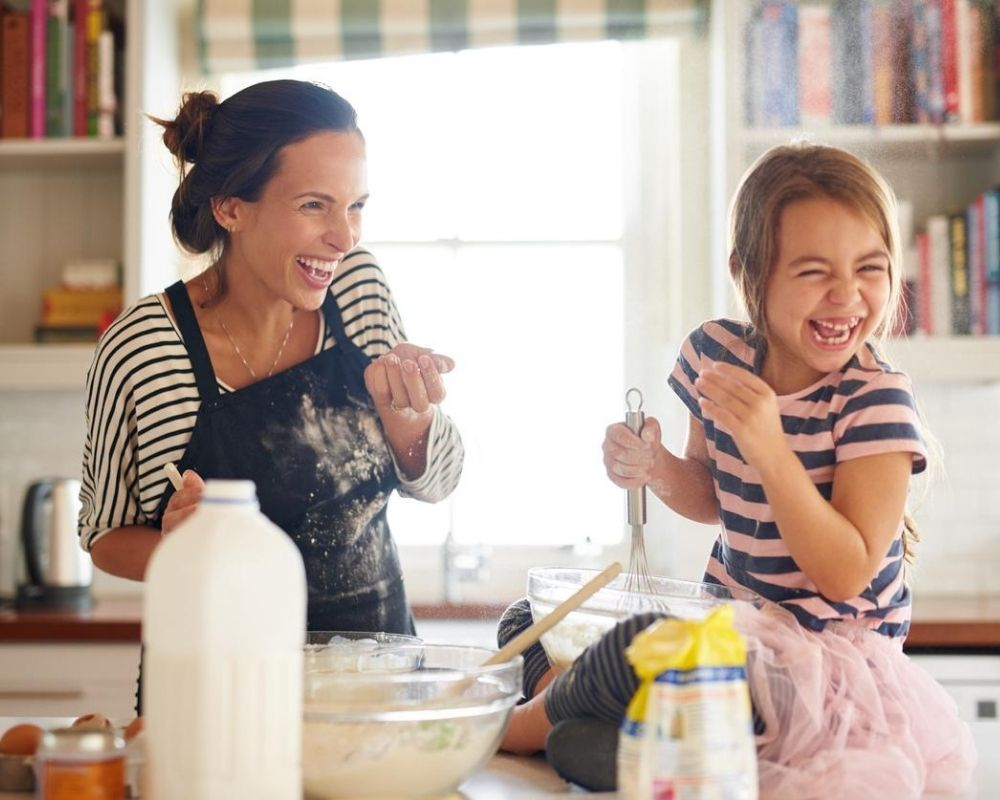 A mother and daughter baking a flourless cake together.