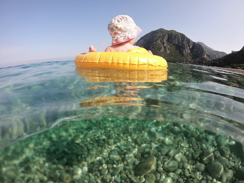 Baby girl in a yellow inflatable ring in floating in the sea.