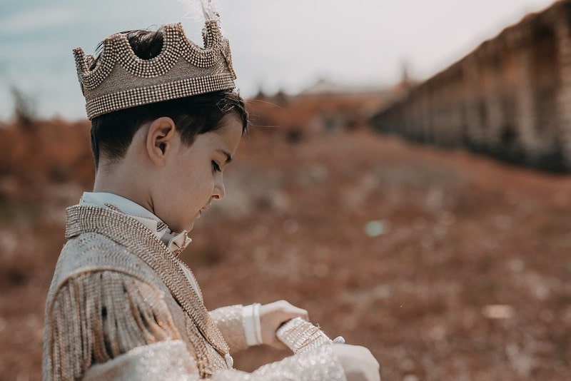 Young boy dressed as a prince with a beaded crown and outfit.