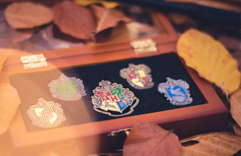 Hogwarts house badges in a wooden box.