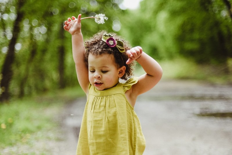Baby girl in a green dress holding a flower in the forest.