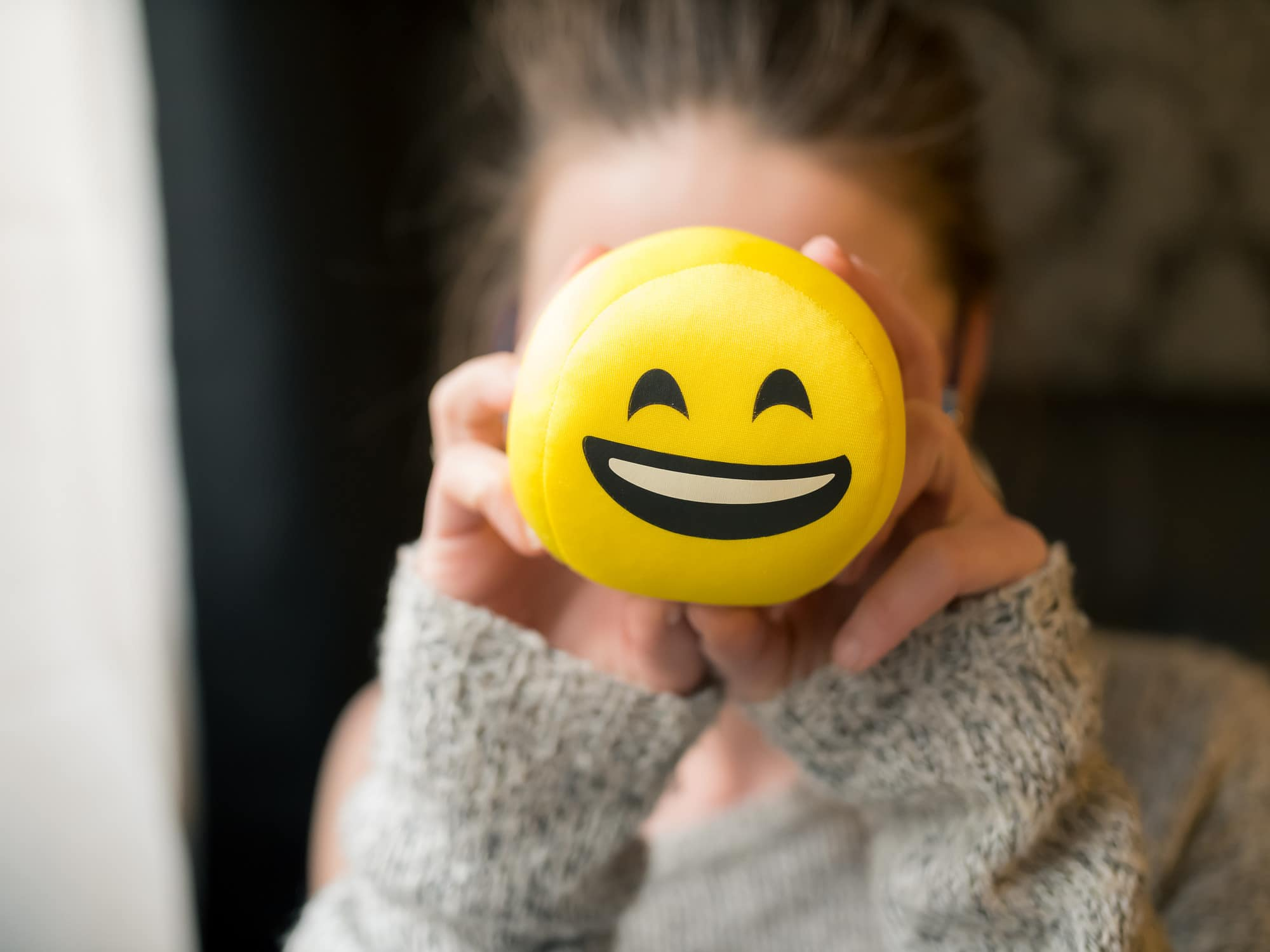 Girl holding a smiley face toy up to her face
