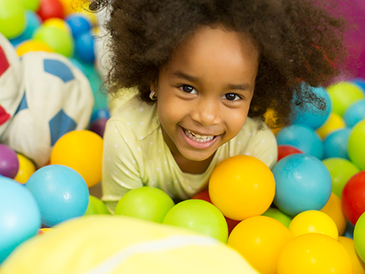 Child in a ball pit at a soft play centre.