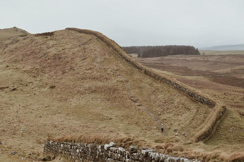 A walker in the distance walking alongside Hadrian's Wall.
