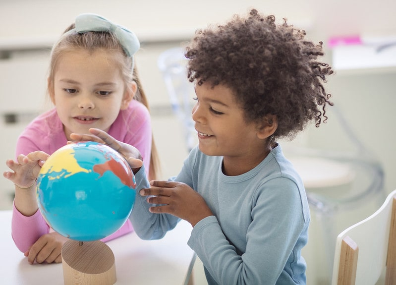 Kids looking at a globe for their non verbal reasoning test.