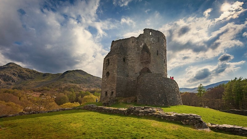 Welsh Castle in the countryside with hills in the background on a sunny day.