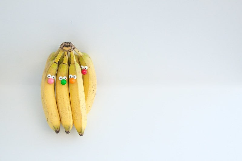 A bunch of bananas with googly eyes stuck on making funny faces.