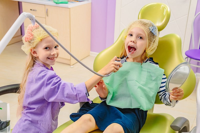 Two little girls playing dentist pretending to use the equipment on each other.