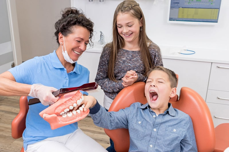 Kids joking around with the dentist, pretending to trap the boy's fingers in giant fake teeth.
