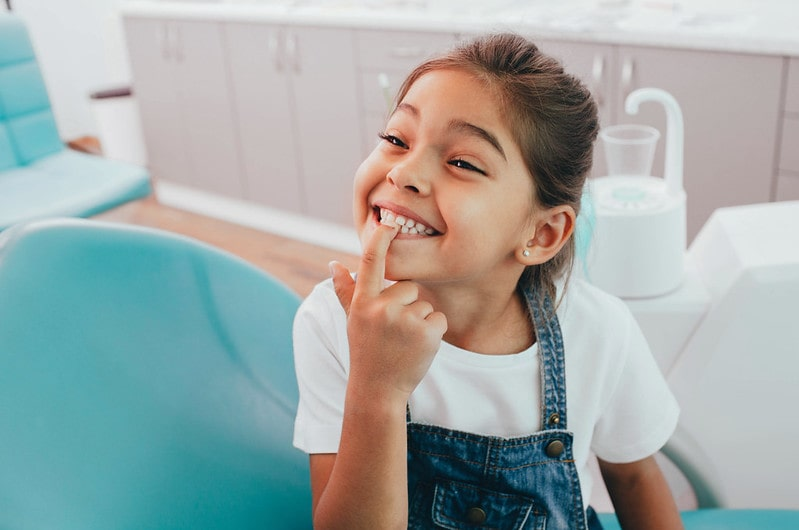 Little girl at dentist smiling and pointing to her teeth.