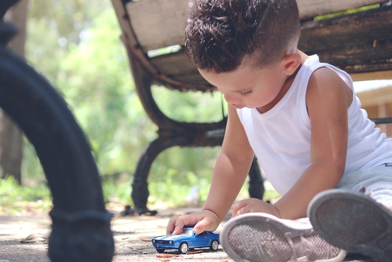Little boy sat on the floor playing with a blue toy car.